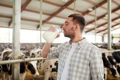 Mężczyzna lub rolnik pije krowy mleko na nabiału gospodarstwie rolnym zdjęcie stock