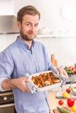 Mężczyzna lub szefa kuchni mienia prażaka naczynie z gorącymi kurczaków drumsticks fotografia royalty free