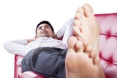 Mężczyzna lying on the beach na kanapie podczas gdy marzący Obrazy Stock