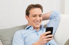 Mężczyzna lying on the beach Na kanapie Z telefonem komórkowym obrazy royalty free