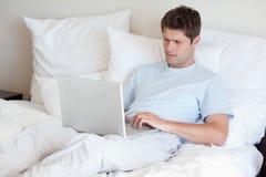 Mężczyzna lying on the beach w łóżku z laptopem zdjęcie royalty free