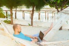 Mężczyzna lying on the beach w hamaku przegapia ocean Facet z zdjęcia stock