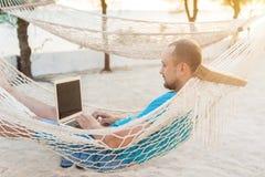 Mężczyzna lying on the beach w hamaku przegapia ocean Facet z obraz royalty free