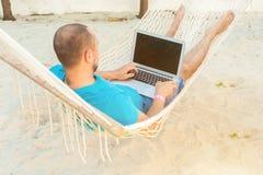 Mężczyzna lying on the beach w hamaku przegapia ocean Facet z obrazy stock