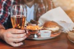 Mężczyzna ma odpoczynek, pije piwo i je hamburger w pab, fotografia stock