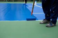 Mężczyzna malarza use farby rolownik maluje tenisowego sądu Obrazy Royalty Free