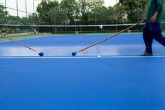 Mężczyzna malarza use farby rolownik maluje tenisowego sądu Zdjęcia Stock