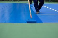 Mężczyzna malarza use farby rolownik maluje tenisowego sądu Zdjęcie Royalty Free