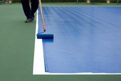 Mężczyzna malarza use farby rolownik maluje tenisowego sądu Obraz Royalty Free