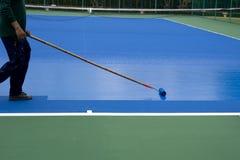 Mężczyzna malarza use farby rolownik maluje tenisowego sądu Fotografia Royalty Free