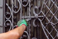 Mężczyzna maluje bramę z forged elementami Na jego ręce jest blisko łokcia pasający zielona rękawiczka, zdjęcia stock