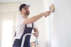Mężczyzna maluje jeden ścianę na drabinie Zdjęcia Royalty Free