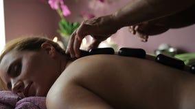Mężczyzna masażysta stawia gorących kamienie na plecy łgarska kobieta w zdroju centrum zbiory wideo
