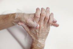 Mężczyzna masuje ręki za pomocą maski - rękawiczka dla ręk obraz royalty free