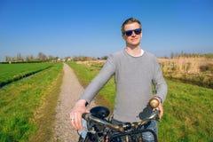 Mężczyzna mienia bicykl w wsi Fotografia Royalty Free