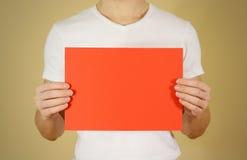 Mężczyzna mienia czerwieni A4 papier horizontally Ulotki prezentacja pam Fotografia Stock