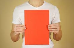Mężczyzna mienia czerwieni A4 papier pionowo Ulotki prezentacja Pamph Zdjęcie Stock