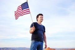 Mężczyzna mienia flaga amerykańska i patrzeć na odległości Zdjęcia Stock