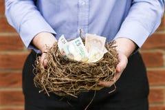 Mężczyzna mienia gniazdeczko pieniądze, horyzontalny Obrazy Stock