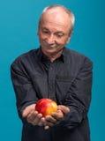 Mężczyzna mienia jabłko w ręce Obrazy Royalty Free