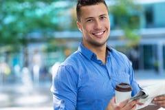 Mężczyzna mienia kawa i gazeta obraz stock