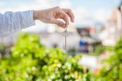 Mężczyzna mienia klucz dom na tle domy w mieście Transakcja z nieruchomości pojęciem Zdjęcie Stock