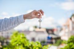 Mężczyzna mienia klucz dom na tle domy w mieście Transakcja z nieruchomości pojęciem Zdjęcia Stock