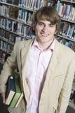 Mężczyzna mienia książki W bibliotece Zdjęcie Stock