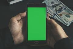 Mężczyzna mienia mobilny mądrze telefon z chroma klucza zieleni ekranem na czarnym tle, nowej technologii pojęcie Fotografia Royalty Free