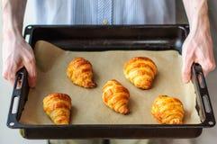 Mężczyzna mienia niecka z świeżymi piec croissants obrazy stock