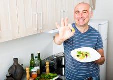 Mężczyzna mienia palce w zielonych oliwkach Fotografia Royalty Free