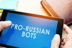 Mężczyzna mienia pastylka z rosjanin larwami Rosyjski internet propagandy pojęcie Zdjęcie Royalty Free