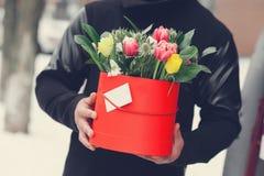 Mężczyzna mienia prezenta czerwony pudełko z pięknym bukietem tulipany i białe chryzantemy z zielonym leav kwitnienia menchii, ko Zdjęcia Royalty Free