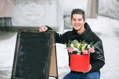 Mężczyzna mienia prezenta czerwony pudełko z pięknym bukietem tulipany i białe chryzantemy z zielonym leav kwitnienia menchii, ko Obraz Royalty Free