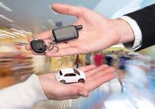 Mężczyzna mienia samochodu klucz, kobieta trzyma małego samochód Zdjęcie Royalty Free