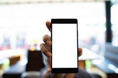 Mężczyzna mienia smartphone z pustym ekranem Bierze twój ekran stawiać zdjęcie stock