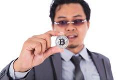Mężczyzna mienia srebra bitcoin w ręce odizolowywającej na białym tle Fotografia Stock