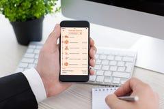 Mężczyzna mienia telefon z app tropi doręczeniowego pakunek na ekranie Fotografia Royalty Free