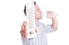 Mężczyzna mienia termometr i pić zimna woda obraz royalty free