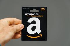 Mężczyzna mienie przeciw szaremu tłu 25 euro amazonki prezenta karta jest Fotografia Royalty Free