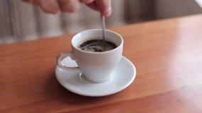 Mężczyzna miesza kawę w filiżance, zakończenie zdjęcie wideo