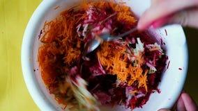 Mężczyzna miesza sałatki marchewka, burak i jabłko, Kulinarna jarska surowa sałatka, zwolnione tempo zbiory