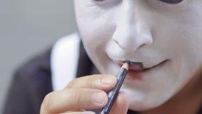 Mężczyzna mima farba jego wargi z czarnym ołówkiem zbiory
