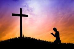 Mężczyzna modlenie pod krzyżem Zdjęcia Royalty Free