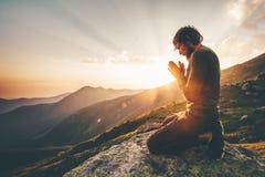 Mężczyzna modlenie przy zmierzch górami obrazy royalty free
