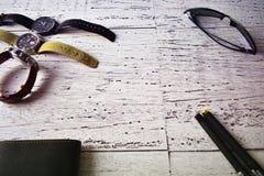 Mężczyzna mody akcesoriów zegarka okularów przeciwsłonecznych portfla stylu życia luksusowego składu nieociosany drewniany tło Fotografia Royalty Free