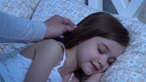 Mężczyzna muska jego córki głowę, ona śpi z bliska zbiory