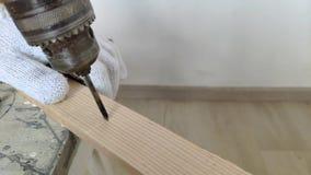 Mężczyzna musztruje drewnianą deskę, świder, beton, elektryczny świder, zakończenie w górę ręk chwyt elektryczny musztruje wewnąt zbiory wideo