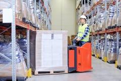 Mężczyzna na forklift ładowania pudełkach przy magazynem obrazy stock