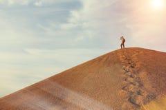 Mężczyzna na górze diuny w pustyni Obraz Stock